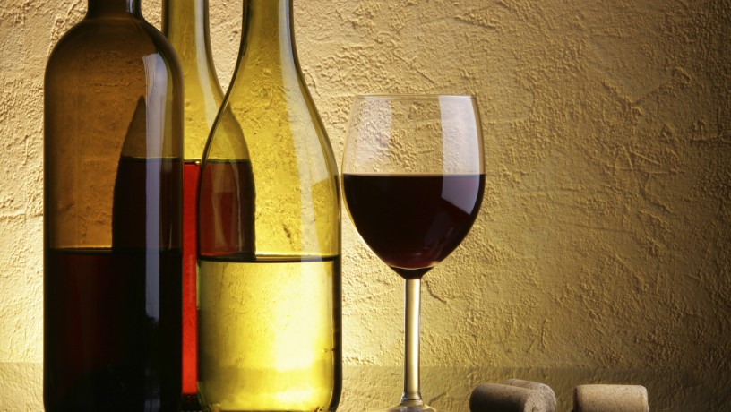 Still-life with three wine bottles and glass over textured background