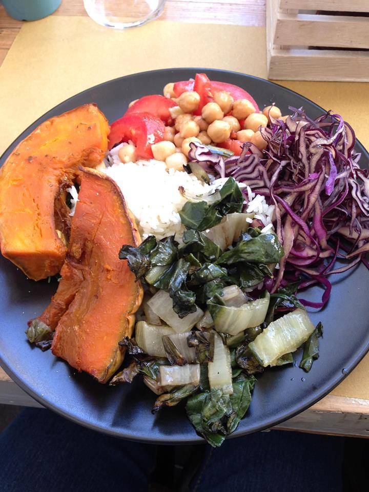 Piatto vegan con riso basmati, zucca arrosto, cavolo cappuccio, erbette, ceci, pomodori, rucola