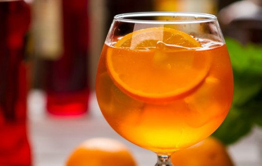 Orange drink in wineglass. Slice of fruit and ice. Chilled aperol spritz. Dry wine and soda water.